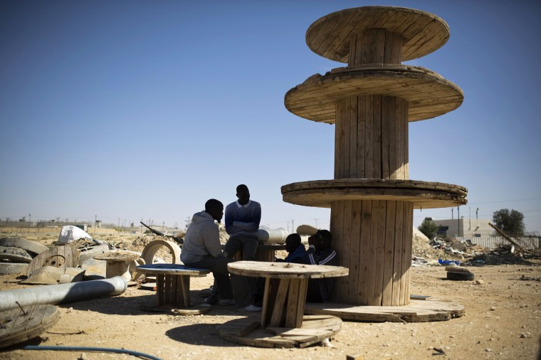 African migrants sit next to stacked wooden reels outside Holot, a detention centre in Israel's southern Negev desert April 11, 2014. Israel opened Holot as part of its bid to rid itself of some of the 50,000 African migrants, mostly Sudanese and Eritreans who have since around 2007 entered territory claimed by the country.  || PHOTO CREDIT: AMIR COHEN  - REUTERS