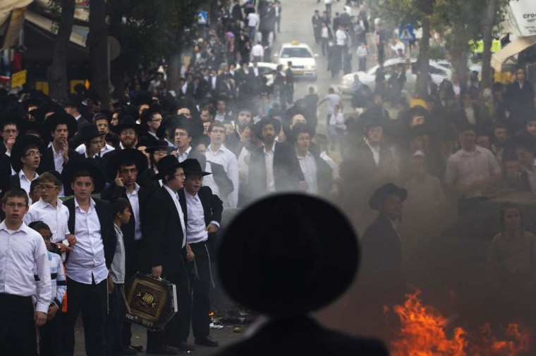 Ultra-Orthodox Jewish men and youths stand next to a fire during a protest in Jerusalem's Mea Shearim neighbourhood April 10, 2014. Hundreds of ultra-Orthodox Jewish men protested on Thursday against the jailing of a Jewish seminary student who failed to comply with a recruitment order. Last month Israel's parliament approved a contentious law that abolishes blanket military exemptions for ultra-Orthodox Jewish seminary students, ending a tradition upheld since the state's foundation. (Ronen Zvulun/Reuters)