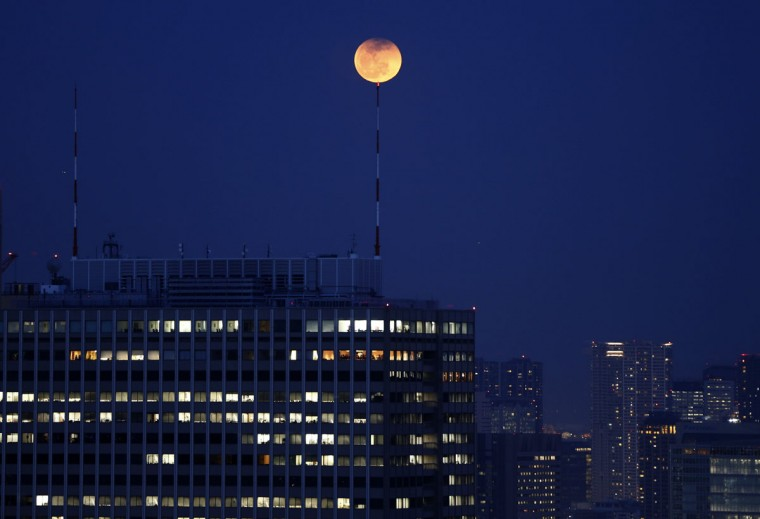 The partial lunar eclipse is seen atop an antenna installed on the roof of a high-rise building in Tokyo on April 15, 2014. (REUTERS/Issei Kato)