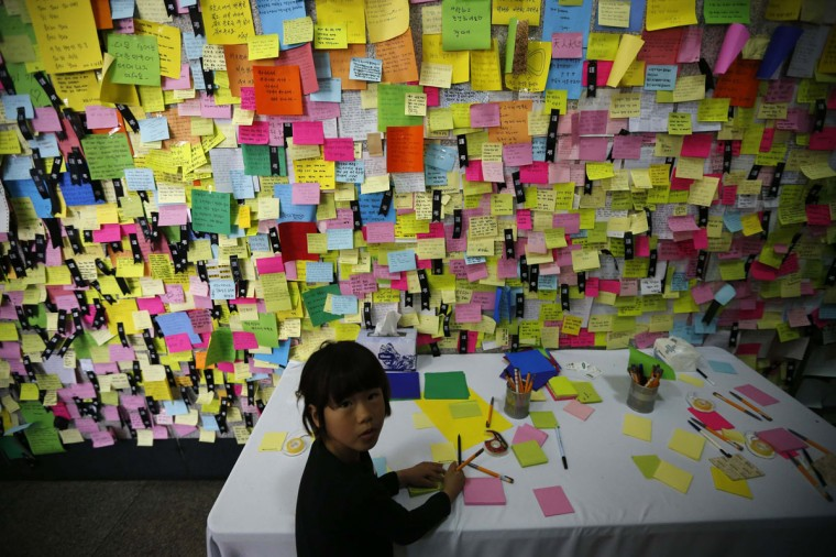 A girl writes a message for victims from capsized passenger ship Sewol, at a temporary group memorial altar for the victims in Ansan April 24, 2014. A South Korean boy whose shaking voice first raised the alarm that the overloaded ferry with hundreds of children on board was sinking has been found drowned in the underwater wreckage of the ship, his parents believe, the coastguard said on Thursday. The Sewol sank on April 16 on a routine trip from the port of Incheon, near Seoul, to the southern holiday island of Jeju. (REUTERS/Kim Hong-Ji)
