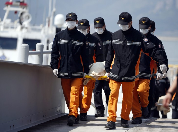 Rescue workers carry the bodies of passengers who were on the capsized Sewol passenger ship, which sank in the sea off Jindo, at a port where family members of missing passengers have gathered, in Jindo April 20, 2014. South Korean prosecutors investigating the ferry disaster said on Sunday they would seek to extend the detention of the ship's captain and two other crew by 10 days as they tried to determine the cause of the accident that may claim more than 300 lives. (Kim Hong-Ji/Reuters)