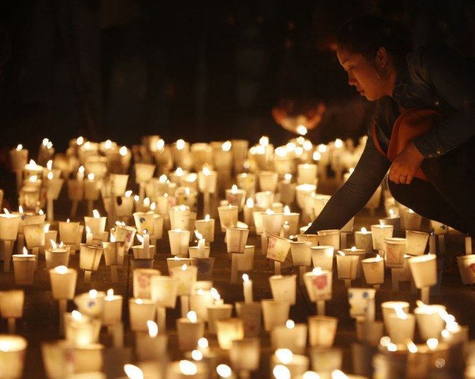 A woman attends a candlelight vigil in Ansan, to commemorate the victims of capsized passenger ship Sewol and to wish for the safe return of missing passengers, April 24, 2014. More than 300 people, most of them students and teachers from the Danwon High School, are dead or missing presumed dead after the April 16 disaster. The confirmed death toll on Thursday was 171. The Sewol ferry, weighing almost 7,000 tons, sank on a routine trip from the port of Incheon, near Seoul, to the southern holiday island of Jeju. Investigations are focused on human error and mechanical failure. (REUTERS/Kim Hong-Ji)
