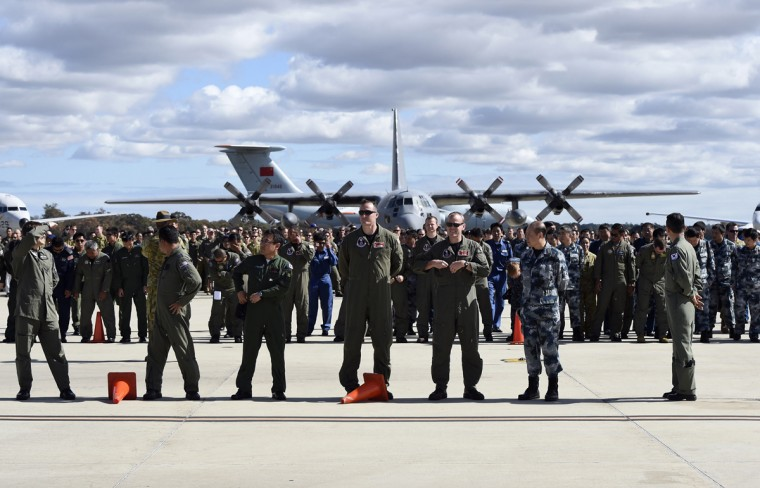 International and Australian air crews involved in the search for missing Malaysia Airlines plane MH370, prepare for an official photograph on the tarmac at the Royal Australian Air Force (RAAF) Pearce Base in Bullsbrook, near Perth April 29, 2014. The chance of finding floating debris from the missing Malaysia Airlines jetliner has become highly unlikely, and a new phase of the search would focus on a far larger area of the Indian Ocean floor, Australian Prime Minister Tony Abbott said on Monday. The international search effort for Malaysia Airlines Flight MH370, which vanished on March 8 with 239 people on board, has so far failed to turn up any trace of wreckage from the plane. Given the amount of time that has elapsed, Abbott said that efforts would now shift away from the visual searches conducted by planes and ships and towards underwater equipment capable of scouring the ocean floor with sophisticated sensors. (Richard Polden/Reuters)