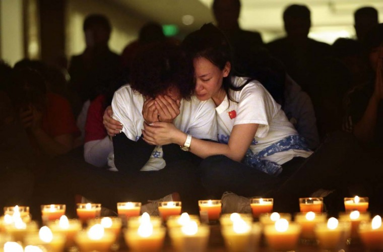 A family member cries as she and other relatives pray during a candlelight vigil for passengers onboard the missing Malaysia Airlines Flight MH370 in the early morning, at Lido Hotel, in Beijing April 8, 2014, after a month of searching for the missing aircraft. An Australian ship searching for a missing Malaysia Airlines jetliner has picked up signals consistent with the beacons from aircraft black box recorders, in what search officials said on Monday was the most promising lead yet in the month-long hunt. (Jason Lee/Reuters)