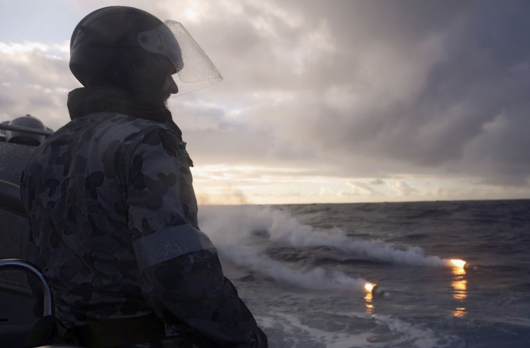 Standing in a rigid hull inflatable boat launched from the Australian Navy ship HMAS Perth, Boatswain's Mate, Able Seaman Morgan Macdonald observes markers dropped from a Royal New Zealand Air Force (RNZAF) P3K Orion after an object was sighted in the southern Indian Ocean during the continuing search for the missing Malaysian Airlines flight MH370 in this picture released by the Australian Defence Force April 17, 2014. The search for the Malaysia Airlines jetliner deep in the Indian Ocean was again cut short on Wednesday when technical problems forced the U.S. Navy underwater drone to surface without finding anything, officials said. An unspecified technical problem meant the Bluefin resurfaced early on Wednesday and analysis of the sonar data downloaded showed no significant detections, the Australian agency leading the search said. (REUTERS/Australian Defence Force/Handout via Reuters)
