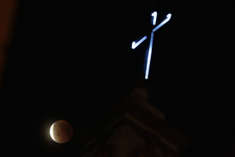 The moon is seen during a total eclipse behind the cathedral in Monterrey on April 15, 2014. (REUTERS/Daniel Becerril)
