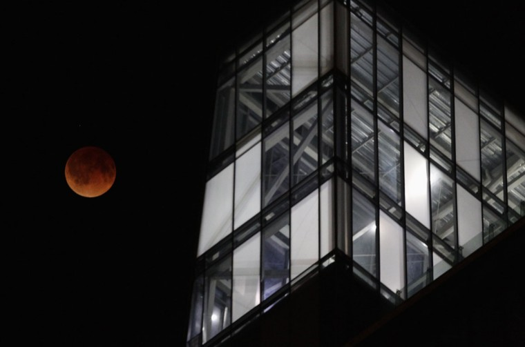 The moon is seen during a total eclipse behind an office building in Monterrey on April 15, 2014. (REUTERS/Daniel Becerril)