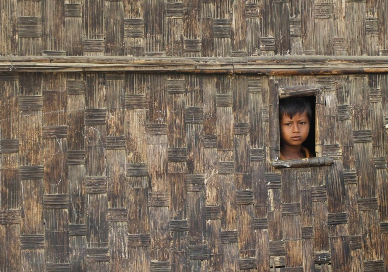 A boy looks from his temporary shelter at a Rohingya refugee camp as Myanmar's government embarks on a national census, in Sittwe. At least 20,000 people in displacement camps around Sittwe will run out of drinking water within 10 days, while food stocks will run out within two weeks, imperiling thousands more. In the absence of nongovernment organizations (NGOs), the United Nations is working with the government to bring emergency supplies to camps, but that is only a short-term solution, said Pierre Peron, a spokesman for the UN Office for the Coordination of Humanitarian Affairs. The evacuation of aid workers came as Myanmar prepared to launch its first census since 1983, which sparked controversy because it included questions on religion and ethnicity. Those are sensitive subjects in a country riven by sectarian tensions and especially in Rakhine, which is home to a million mostly stateless Rohingya whom the government refers to as Bengali, implying they are illegal immigrants from Bangladesh. (Soe Zeya Tun/Reuters)