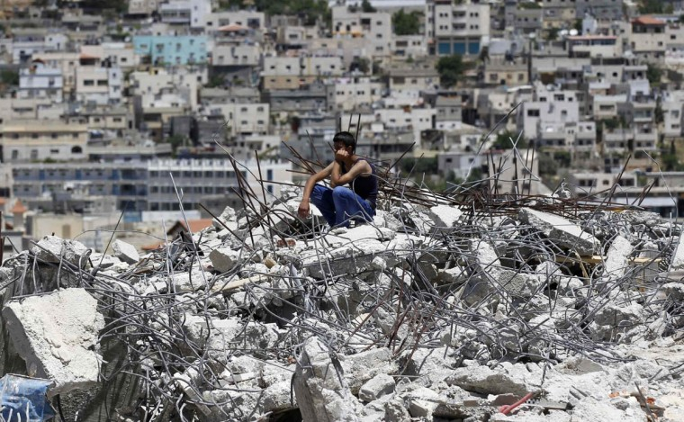 "A Palestinian sits on top of the rubble of a house under construction after it was demolished by Israeli bulldozers at Al-Aroub refugee camp, near the West Bank City of Hebron. Israeli military said that ""security forces carried out the demolition of two construction sites that were built illegally in Al-Aroub. The sites were demolished after the residents' requests for building permits were refused due to non-compliance with the required (construction) regulations."" (Ammar Awad/Reuters photo)"