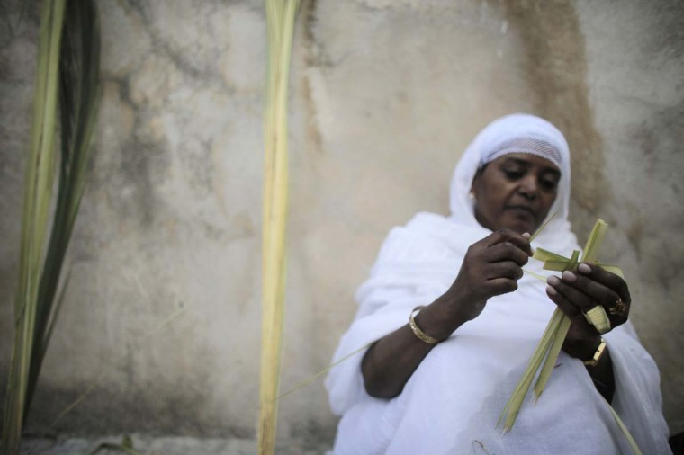 An Ethiopian Orthodox worshipper folds palm fronds into a cross before the Palm Sunday procession outside the Ethiopian section of the Church of the Holy Sepulchre in Jerusalem's Old City April 13, 2014. (Ammar Awad/Reuters)