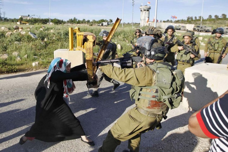 A Palestinian woman scuffles with an Israeli soldier as she tries to open a gate leading to the entrance of Nabi Saleh village, near the West Bank city of Ramallah April 14, 2014. (Mohamad Torokman/Reuters)