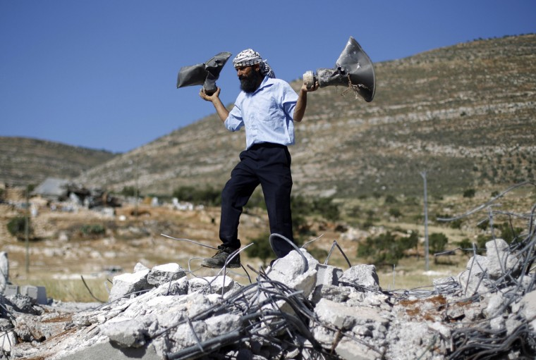 A Palestinian man holds damaged loudspeakers belonging to a mosque after it was demolished by Israeli bulldozers in Khirbet Al-Taweel village near the West Bank City of Nablus April 29, 2014. Israeli forces demolished several structures, including a mosque, in a Palestinian village on Tuesday, the day a deadline for a deal in now-frozen peace talks expired.A Reuters correspondent witnessed several hundred soldiers deployed in Khirbet al-Taweel, in the occupied West Bank, around daybreak. They guarded six bulldozers that reduced to rubble buildings that were constructed without Israeli permits. Palestinians say such documents are nearly impossible to obtain. (Mohamad Torokman/Reuters)