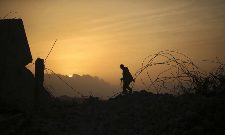 A Palestinian man walks atop a destroyed building during sunset in the northern Gaza Strip April 7, 2014. (Mohammed Salem/Reuters)