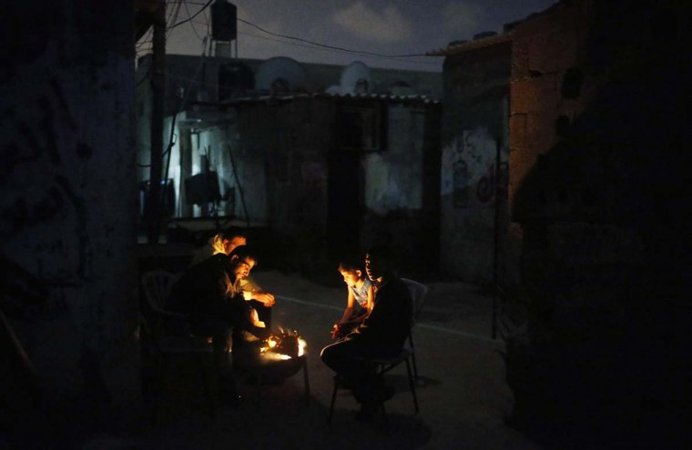 Palestinians gather around a fire at Shati refugee camp in Gaza City April 7, 2014. (Mohammed Salem/Reuters)