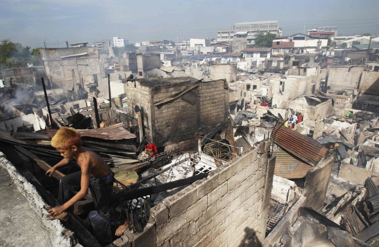 A boy climbs out of a charred shanty as he collects reusable materials after a fire razed through a slum area in Caloocan City, Metro Manila April 21, 2014. The fire left one dead and displaced an estimated 1,000 families and at least 400 houses were destroyed during the fire, a local media reported. (Romeo Ranoco/Reuters)