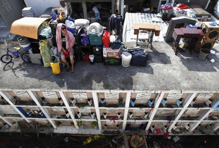"""A woman guards her belongings placed on top of """"apartment-styled"""" tombs after a fire razed through a slum area in Caloocan City, Metro Manila April 21, 2014. The fire left one dead and displaced an estimated 1,000 families and at least 400 houses were destroyed during the fire, a local media reported. (Romeo Ranoco/Reuters)"""