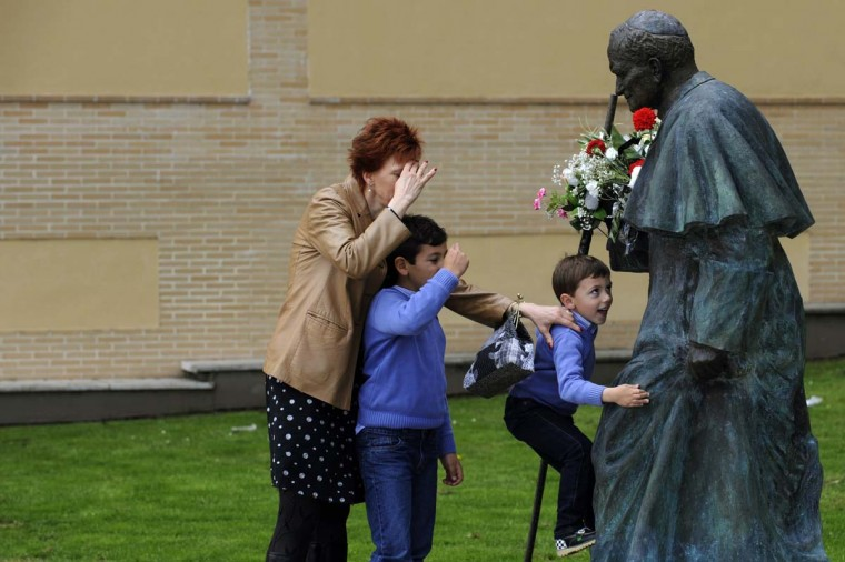 A woman and two children pray in front of a sculpture of Pope John Paul II in Oviedo, northern Spain April 27, 2014. Pope Francis proclaimed his predecessors John XXIII and John Paul II saints in front of more than half a million pilgrims in the Vatican on Sunday, hailing both as courageous men who withstood the tragedies of the 20th century. (Eloy Alonso/Reuters)