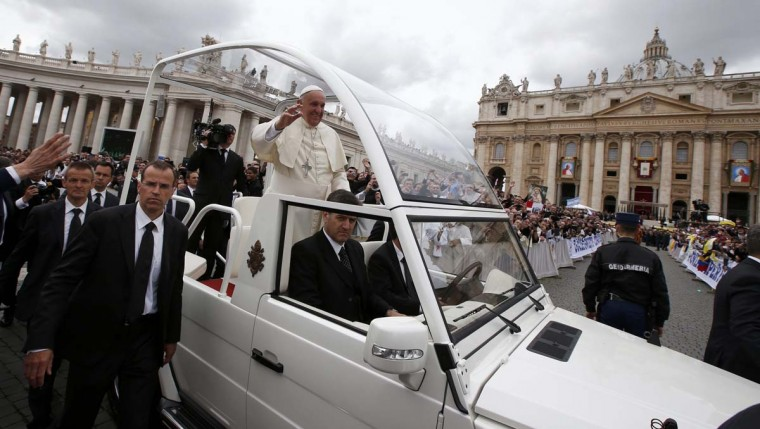 Pope Francis greets the faithful as he rides in his Popemobile after the canonisation ceremony of Popes John XXIII and John Paul II in St Peter's Square at the Vatican, April 27, 2014. Pope John XXIII, who reigned from 1958 to1963 and called the modernising Second Vatican Council, and Pope John Paul II, who reigned for nearly 27 years before his death in 2005 and whose trips around the world made him the most visible pope in history, were declared saints by Pope Francis at an unprecedented twin canonisation on Sunday. (Tony Gentile/Reuters)