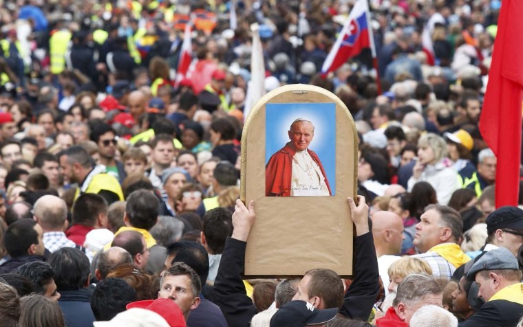 A Catholic faithful raises an image of Pope John Paul II through the crowds waiting to attend the canonisation ceremony of Popes John XXIII and John Paul II in St. Peter's Square at the Vatican April 27, 2014. Pope John XXIII, who reigned from 1958 to 1963 and called the modernising Second Vatican Council, and Pope John Paul II, who reigned for nearly 27 years before his death in 2005 and whose trips around the world made him the most visible pope in history, will be declared saints by Pope Francis at an unprecedented twin canonisation on Sunday. (Remo Casilli/Reuters)