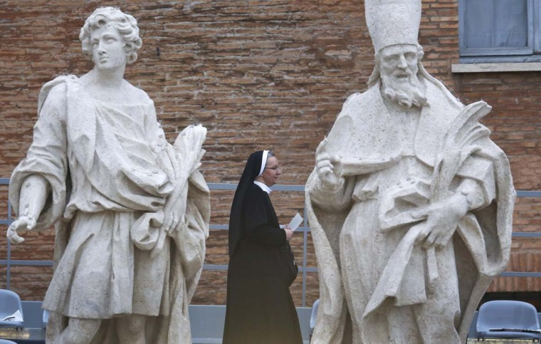 A nun walks past statues on the colonnade of St. Peter's Square before a canonisation ceremony at the Vatican April 27, 2014. Pope John XXIII, who reigned from 1958 to 1963 and called the modernising Second Vatican Council, and Pope John Paul II, who reigned for nearly 27 years before his death in 2005 and whose trips around the world made him the most visible pope in history, will be declared saints by Pope Francis at an unprecedented twin canonisation on Sunday. (Stefano Rellandini/Reuters)