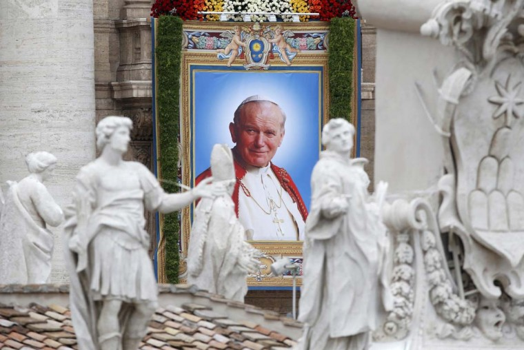 A tapestry portrait of Pope John Paul II hanging from the facade of St Peter's Basilica is seen across the colonnade roof during the canonisation ceremony at the Vatican, April 27, 2014. Pope John XXIII, who reigned from 1958 to1963 and called the modernising Second Vatican Council, and Pope John Paul II, who reigned for nearly 27 years before his death in 2005 and whose trips around the world made him the most visible pope in history, were declared saints by Pope Francis at an unprecedented twin canonisation on Sunday. (Stefano Rellandini/Reuters)