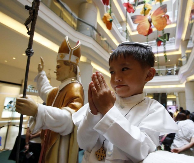A boy clasps his hands next to a statue of Pope John Paul II at an exhibit of Pope's relics in Quezon city, Metro Manila April 27, 2014. Pope John XXIII, who reigned from 1958 to1963 and called the modernising Second Vatican Council, and Pope John Paul II, who reigned for nearly 27 years before his death in 2005 and whose trips around the world made him the most visible pope in history, will be declared saints by Pope Francis at an unprecedented twin canonisation on Sunday. (Erik De Castro/Reuters)