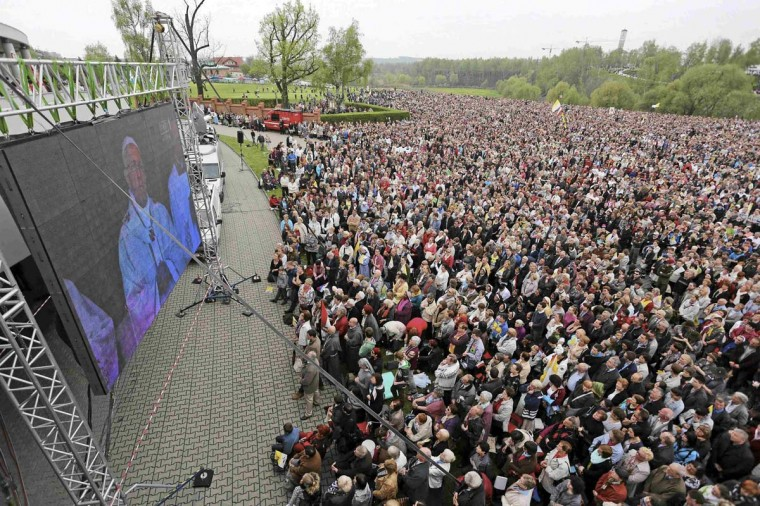 Catholic faithful watch the canonisation of Pope John XXIII and John Paul II on a giant screen near the Sanctuary of Divine Mercy, where Karol Wojtyla was archbishop before becoming Pope John Paul II, in Krakow April 27, 2014. Pope Francis proclaimed his predecessors John XXIII and John Paul II saints on Sunday, hailing both as courageous men who withstood the tragedies of the 20th century. (Mateusz Skwarczek/Agencja Gazeta)