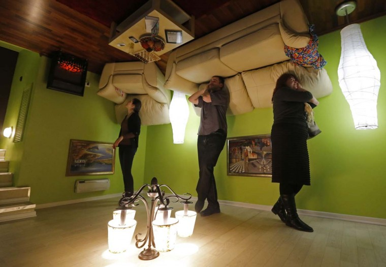 """People take a tour in an """"upside down home"""" in St. Petersburg April 10, 2014. The exhibition charges less than $10 for a walk through its three rooms and two bathrooms through the apartment. (Alexander Demianchuk/Reuters)"""