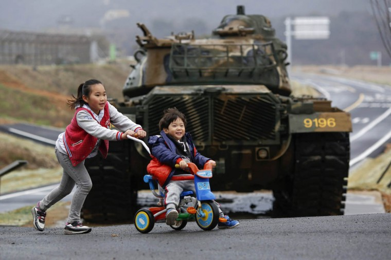 Children play in front of a tank on the island of Baengnyeong, which lies on the South Korean side of the Northern Limit Line (NLL), in the Yellow Sea. Baengnyeong, closer to Pyongyang than Seoul, is an isolated and heavily militarized island whose resident live in constant fear of possible clashes between two armies. The beaches of Baengnyeong are often walled with barbed wire fences straddling the sand dunes with intermittent holes for machine gun positions. The Northern Limit Line, a disputed maritime border that wraps itself round a part of the North's coastline, has been the scene of frequent clashes between South and North Korea. The line was drawn up at the end of the 1950-53 Korean War and North Korea does not recognize it. The two sides are still technically at war as the conflict ended in a mere truce, not a treaty. (Damir Sagolj/Reuters photo)
