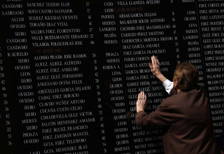 A woman touches the names of her family in front of a memorial for Republicans killed during and after the 1936-1939 Spanish civil war, in Oviedo, northern Spain April 14, 2014. Spain celebrates today the 83rd anniversary of the proclamation of the 2nd Spanish Republic, which was overthrown by dictator Francisco Franco in a three-year civil war that claimed half a million lives. (Eloy Alonso/Reuters)
