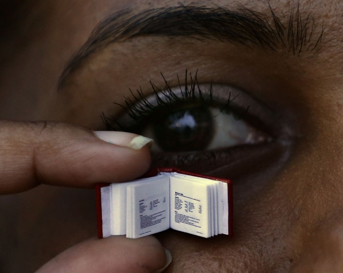 A woman holds up the small recipe book by Sri Lanka's iconic chef Publis Silva in Colombo April 24, 2014. The book is about 1cm by 1 cm (0.39 inch by 0.39 inch) and weight about 5 milligrams (0.00018 ounce), and there be 40 copies of it. (REUTERS/Dinuka Liyanawatte)
