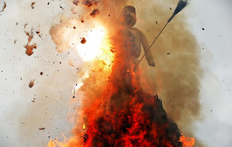 """The Boeoegg, a snowman made of wadding and filled with firecrackers, burns atop a bonfire in the Sechselaeuten square in Zurich April 28, 2014. As the bells of St. Peter's church chime six o'clock, the bonfire below the """"Boeoegg"""" is set alight and mounted guildsmen gallop around the pyre to the tune of the Sechselaeuten March. The faster the head of the """"Boeoegg"""", the symbol of winter, catches fire and explodes, the warmer and more beautiful the summer will be. (Arnd Wiegmann/Reuters)"""