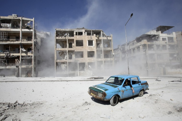 Men drive a car near a site hit by what activists said was an air strike by government forces in Aleppo's al-Ansari al-Sharqi neighborhood. (Ammar Abdullah/Reuters)