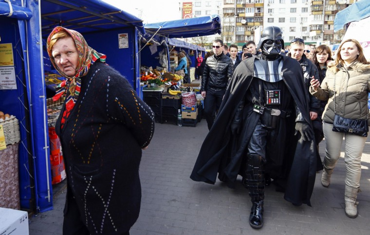 """Darth Vader"", the leader of the Internet Party of Ukraine, walks across a street market near the Ukrainian Central Elections Commission in Kiev. (Shamil Zhumatov/Reuters)"
