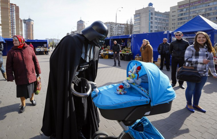 """Darth Vader"", the leader of the Internet Party of Ukraine, looks at a child in a pram at a street market near the Ukrainian Central Elections Commission in Kiev. (Shamil Zhumatov/Reuters)"