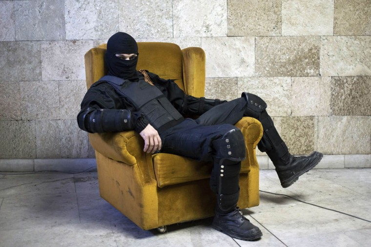 A masked pro-Russian protester sits on a chair as he poses for a picture inside a regional government building in Donetsk, eastern Ukraine. (Marko Djurica/Reuters photo)