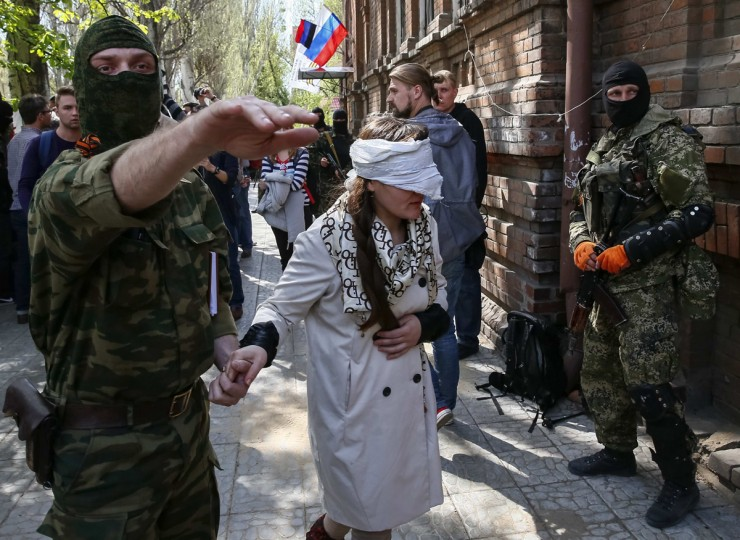 """A pro-Russian armed man escorts Ukrainian journalist Irma Krat after news conference in Slaviansk, April 21, 2014. Pro-Russian separatists in eastern Ukraine have detained a Ukrainian journalist, accusing her of """"war crimes"""" during the """"Euromaidan"""" protests that toppled the Moscow-backed president, her lawyer said on Monday. Krat, 29, was held late on Sunday by militants in the city of Slaviansk, said Oleg Veremienko, a lawyer for the online television news site Krat runs. Russian Internet channel Life News posted video of her being escorted by masked men in combat gear and of an activist saying she was under arrest. (Gleb Garanich/Reuters)"""