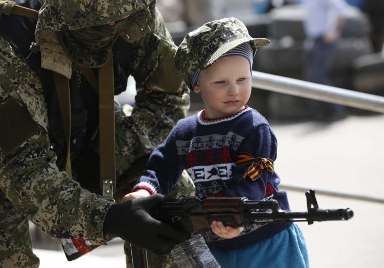 A pro-Russian armed man lends his weapon to a boy posing for a picture for his father in front of the seized town administration building in Kostyantynivka April 28, 2014. Armed pro-Russian separatists who took control of the police headquarters in the east Ukrainian town of Kostyantynivka have also seized the town administration building, a spokesman for the regional government said. (Marko Djurica/Reuters)