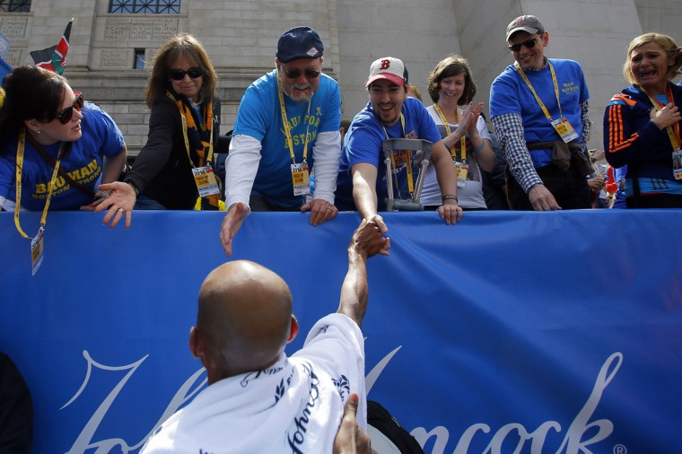 Meb Keflezighi of the U.S. (bottom) is congratulated by 2013 Boston Marathon bombing survivor Jeff Bauman (top C) after winning the 118th running of the Boston Marathon in Boston, Massachusetts April 21, 2014. (Brian Snyder/Reuters)