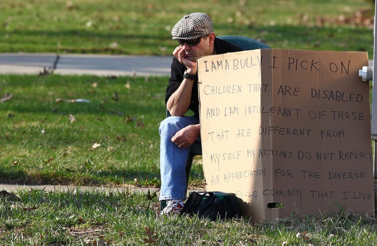 "Edmond Aviv, 62, sits with a sign he made at a street corner in the Cleveland suburb of South Euclid, Ohio. Aviv, who called his neighbor ""Monkey Mama"" as she held her adopted, disabled African-American children, and has smeared dog feces on their wheelchair ramp, was ordered by a judge to carry an ""I AM A BULLY!"" sign on the busy street on Sunday. (Aaron Josefczyk/Reuters)"