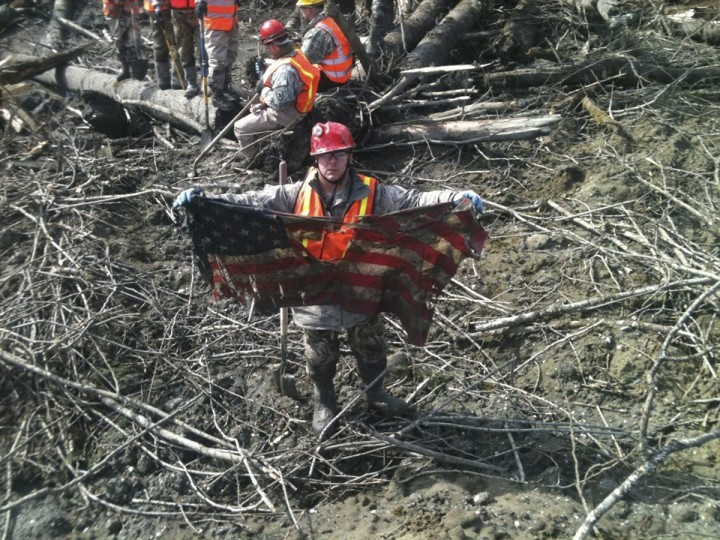 Staff Sgt. Michael Cohan from the 141st Logistical Readiness Squadron based out of Fairchild Air Force Base in Washington, uncovers a tattered American flag and displays it after pulling on a thin red string buried in a pile of debris from the massive mudslide that struck Oso, Washington, March 31, 2014. Survivors of a mudslide that left dozens dead or missing in Washington state said they would like to turn the disaster site into a shrine for the victims once bulldozers clear away the mud and debris. Picture taken March 31, 2014. (Kevin Borden/U.S. Department of Defense/Handout/Reuters)