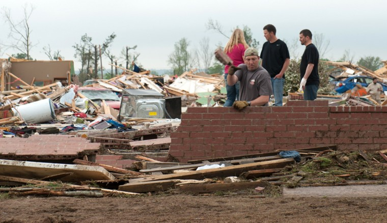 A man casts aside bricks while searching in the rubble of a destroyed house after a tornado hit the town of Vilonia, Arkansas April 28, 2014. Workers searched for survivors on Monday in the rubble left by a wave of tornadoes that ripped through the south-central United States a day earlier, killing at least 18 people in Arkansas, Oklahoma and Iowa. (Angie Davis/Reuters)