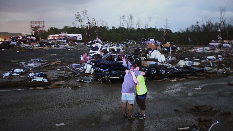 Lori Berseth (R) is consoled after searching for her missing Black Labrador dog, Lucille, after a tornado destroyed the town of Mayflower, Arkansas, April 27, 2014. At least six people were killed on Sunday when a tornado ripped through two Arkansas counties north of Little Rock, authorities said. The fatalities occurred in Faulkner and Pulaski Counties, north of Little Rock, according to law enforcement officials. The governor's office reported that the U.S. National Guard had been dispatched to the scene. (Kathryn Piotrowski/TwisterChasers.com/Reuters)