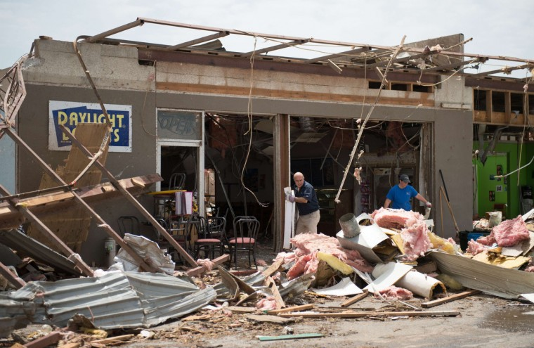 Men clear debris from a destroyed shop a day after a tornado hit the town of Vilonia, Arkansas April 28, 2014. Workers searched for survivors on Monday in the rubble left by a wave of tornadoes that ripped through the south-central United States a day earlier, killing at least 18 people in Arkansas, Oklahoma and Iowa. (Angie Davis/Reuters)