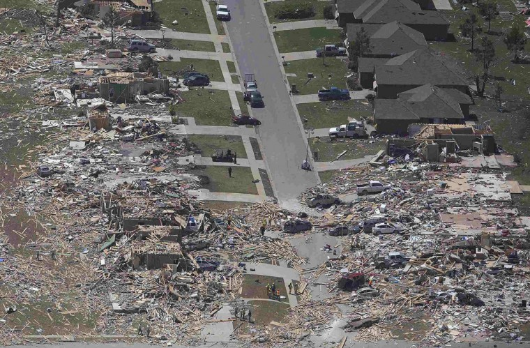 People sift through the rubble of what is left of homes after a tornado hit the town of Vilonia, Ark, April 28, 2014. Workers searched for survivors on Monday in the rubble left by a wave of tornadoes that ripped through the south-central United States a day earlier, killing at least 18 people in Arkansas, Oklahoma and Iowa. (Carlo Allegri/Reuters)