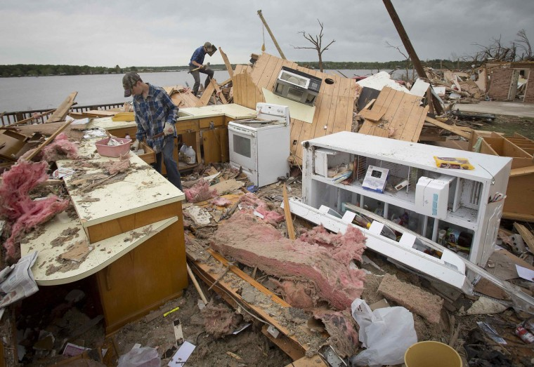 Workers clear debris from what used to be the kitchen and look for treasured articles at Darwin Henry's house in Mayflower, Arkansas April 29, 2014. Henry who had lived in the lakeside home for 27 years said he was happy his wife had passed on last year and didn't have to witness the destruction. At least 30 people across six states were killed in tornadoes unleashed by a vicious storm system that levelled towns and was threatening to cause more mayhem in heavily populated parts of the U.S. South on Tuesday. (Carlo Allegri/Reuters)