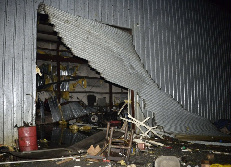 Debris is seen at a damaged business after a tornado hit the town of Mayflower, Arkansas around 7:30 pm CST, late April 27, 2014. Tornadoes ripped through the south-central United States on Sunday, killing at least 12 people in Arkansas and Oklahoma and wiping out entire neighborhoods of homes, according to officials, as rescue workers searched in darkness for survivors. In Mayflower, some of about 45 homes were destroyed in a newer subdivision and a lumberyard was damaged, said Will Elder, an alderman in the city of 2,300 people. (Gene Blevins/Reuters)
