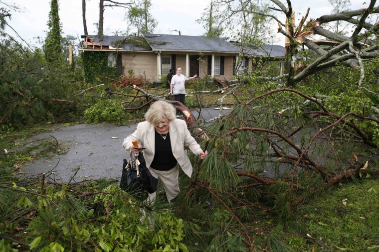 Cathy Norman tries to climb through debris and get to her house on Marquette Street in Tupelo, Mississippi April 28, 2014. On a second day of ferocious storms that have claimed at least 19 lives in the southern United States, a tornado tore through the Mississippi town of Tupelo on Monday causing widespread destruction to homes and businesses, according to witnesses and local emergency officials. (Thomas Wells/Reuters)