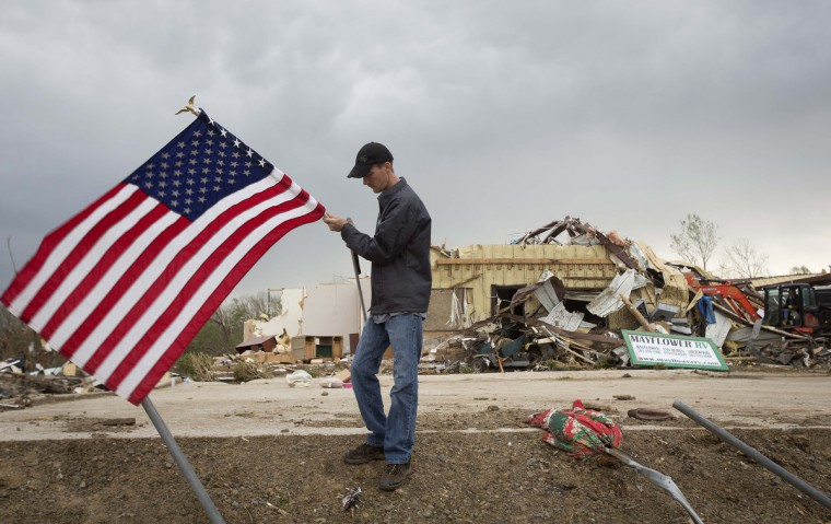Casey Holliman moves a U.S. flag after from it was torn down from a portion of a building at Mayflower RV in Mayflower, Arkansas April 29, 2014. A storm system that killed more than 20 people continued its march across a large swath of the U.S. Southeast on Tuesday, packing baseball-sized hail, damaging winds and the threat of more tornados, meteorologists said. (Carlo Allegri/Getty Images)