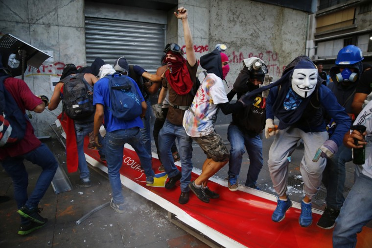 """Anti-government protesters jump and step on a banner of Banco de Venezuela after bringing down the banner during riots in Caracas April 20, 2014. Masked youths battled police, protesters burned and hung from lamp-posts effigies of President Nicolas Maduro and marchers demanded the """"resurrection"""" of democracy on a volatile Easter Sunday in Venezuela. (Jorge Silva/Reuters)"""